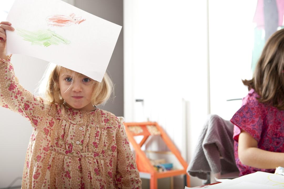 niña agarra un folio con su dibujo en casa